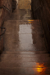 Rain soaked wet stairs descending to the brick cobblestone walkway