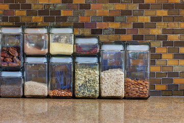 A kitchen in a home with a tiled wall, and counter top with food storage containers