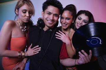 Multi-ethnic women flirting with nightclub DJ