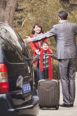 Chinese mother and son greeting returning father