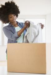 Mixed race woman placing sweater in cardboard box