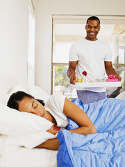 African man bringing wife breakfast in bed