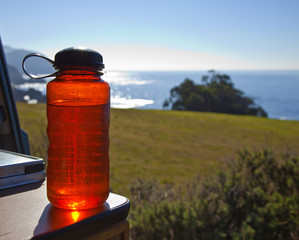 Red Water Bottle with Ocean in Background
