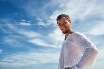 man standing before blue skies with clouds