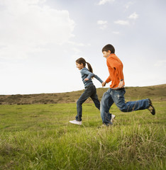 Hispanic sister and brother running in field