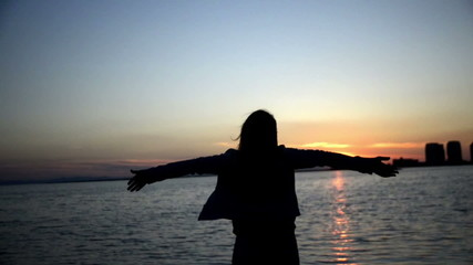 Woman open arms in the dusk.