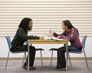 Multi-ethnic college students studying at table