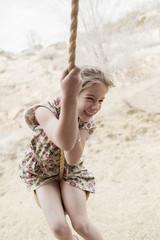 Caucasian girl on rope swing