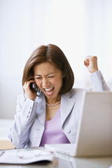 Asian businesswoman cheering on cell phone