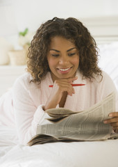 African woman reading newspaper