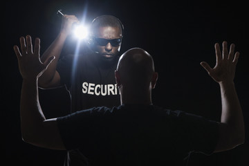 African security guard stopping bald man