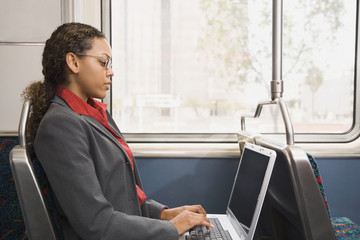 African businesswoman working on train