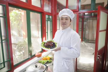 Chinese cook showing food in kitchen