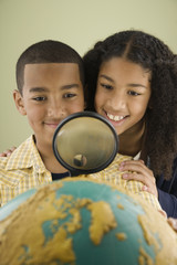 Mixed Race siblings looking at globe through magnifying glass