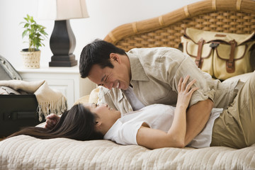 Asian couple hugging on bed