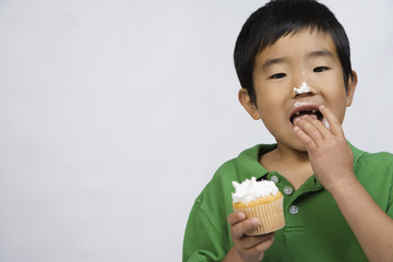 Korean boy eating cupcake