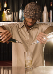 African bartender pouring a mixed drink