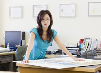 Asian businesswoman leaning on desk
