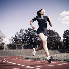 African American woman running on track