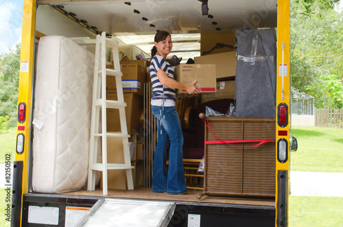 Pretty woman loading a full moving truck - 82150502