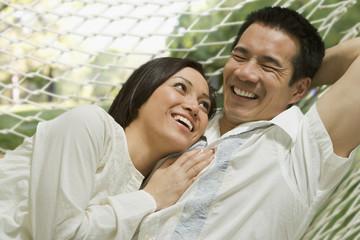 Asian couple laying in hammock