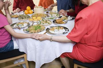 Asian family praying at dinner table