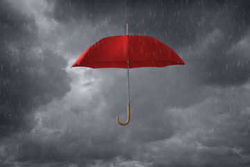 Red umbrella floating in storm clouds