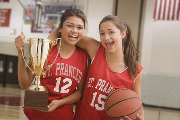 Multi-ethnic girls with trophy hugging in basketball uniforms