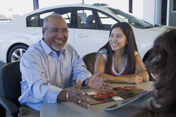 Hispanic father and daughter in car dealership