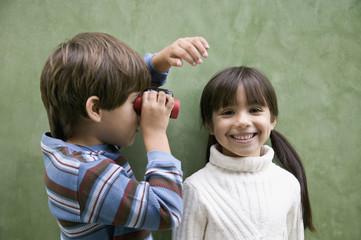 Hispanic boy looking at sister through binoculars