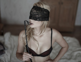 Sexy blonde woman with lace eye cover and whip