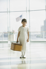 Hispanic girl with suitcase waiting in airport