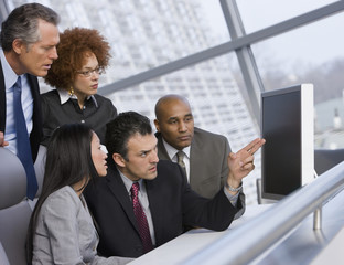 Multi-ethnic businesspeople looking at computer screen