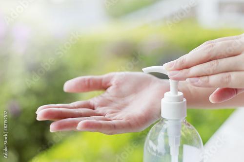 Female hands using wash hand sanitizer gel pump dispenser. - 82152512