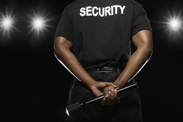 African security guard holding flashlight