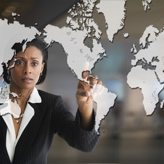 African businesswoman pointing to world map