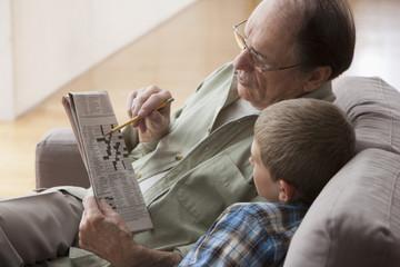 Older Caucasian man and grandson doing crossword puzzle