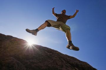 Hispanic man jumping off rock