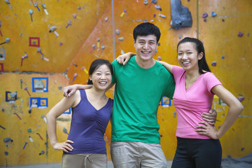 Chinese friends smiling in rock climbing gym