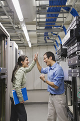 Multi-ethnic coworkers high-fiving in computer server room