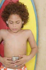 Mixed Race boy listening to mp3 player on surfboard