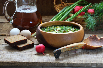 Okroshka with kvass in a wooden bowl and a wooden spoon