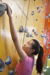 Chinese woman scaling rock wall