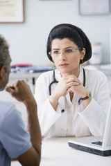 Middle Eastern female doctor talking to patient