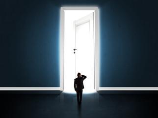 Business man looking at big bright opened door