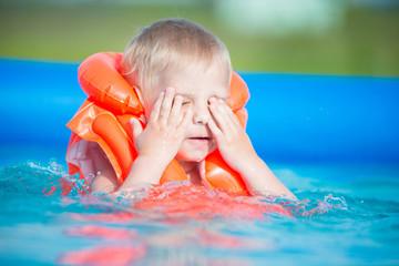 Pretty little boy in swimming pool