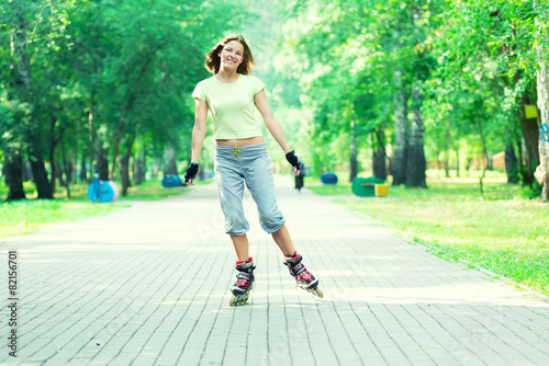 Roller skating sporty girl in park rollerblading on inline skate - 82156701