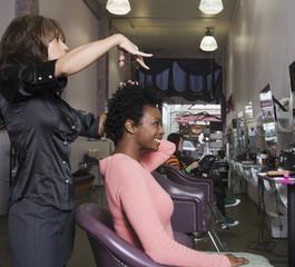 Hispanic hair stylist cutting African woman's hair
