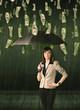 Businesswoman standing with umbrella in dollar bill rain concept