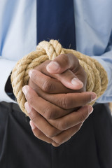 Mixed race businessman with hands tied